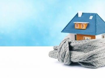 Abitazione avvolta in una sciarpa di lana con sfondo azzurro, simboleggia l'isolamento termico interno di una casa