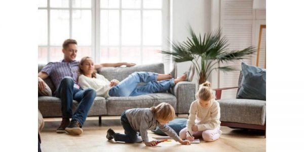 famiglia in salotto con i bambini che giocano sul tappeto